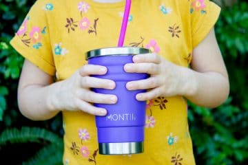 child holding smoothie cup and drinking a smoothie