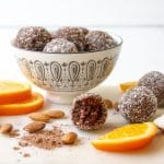 picture of a bowl of chocolate orange almond bliss balls styled with the ingredients placed around the outside.