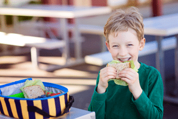 picture of boy smiling and eating sandwich: the best for for kids teeth in the lunchbox