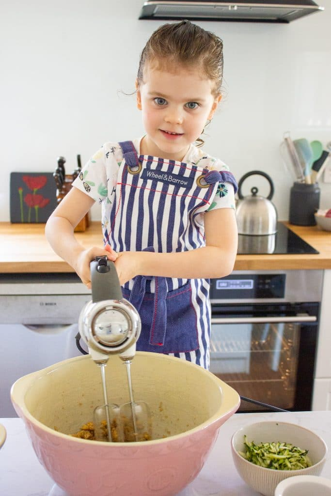 a child is creaming sugar and butter to make healthier monster cookies