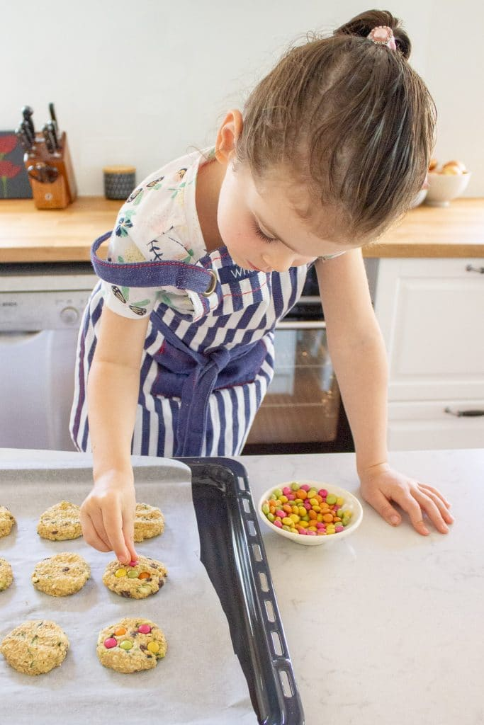 A child is topping the healthier monster cookies with smarties.