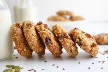 Seedy Oatmeal Sultana Cookies stacked against a milk jar