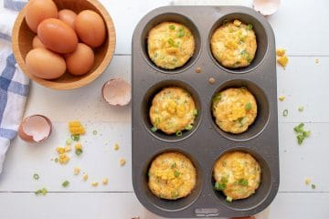 Muffin tin frittatas cooked with bowl of fresh eggs