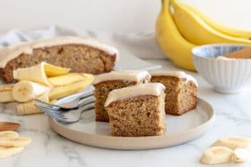 cut banana cake iced with cinnamon cream cheese icing